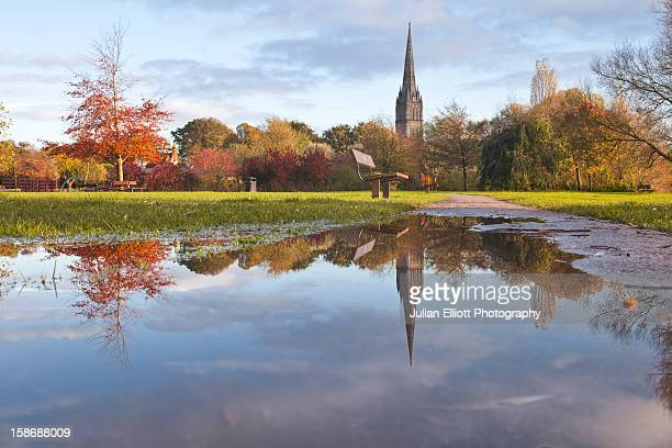 Salisbury cathedral reflecting in a puddle.
