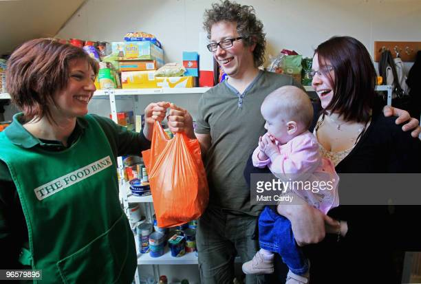 Salisbury foodbank volunteer Lizzie Abnett hands over a donation of food at the foodbank centre and cafe to recently umemployed Alex Korbey his wife...
