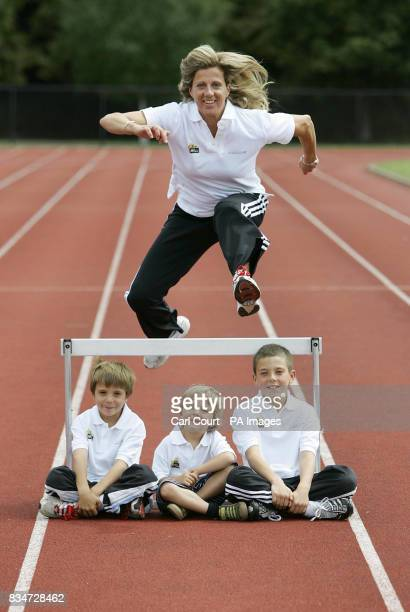 Sally Gunnell the 1992 Olympic 400m hurdles champion jumps over her children Luca aged 7 Marley aged 3 and Finley aged 10 at the Millennium Arena in...