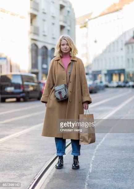 Sally Jo Ringhof wearing a Gucci bag denim jeans beige wool coat shopping bag pink turtleneck on March 24 2017 in Berlin Germany