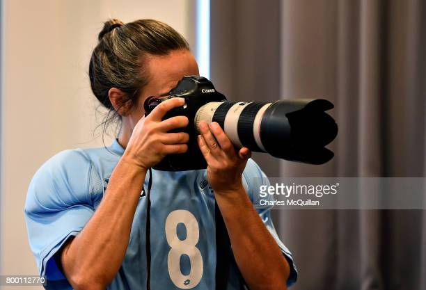 Sally Rutherford of New Zealand points the camera at fellow team mates during a player portrait photo session for FINTRO Hockey World League on June...