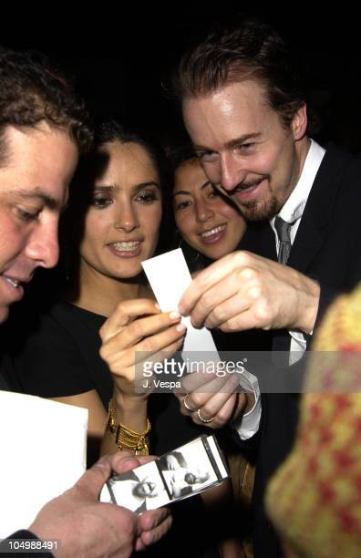 Salma Hayek and Edward Norton look at their photobooth photos