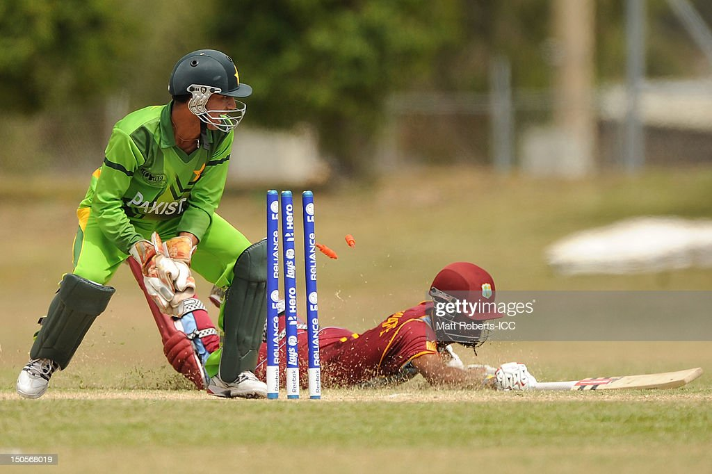 Salman Afridi of Pakistan knocks the bails off as <a gi-track='captionPersonalityLinkClicked' href=/galleries/search?phrase=Kraigg+Brathwaite&family=editorial&specificpeople=6681140 ng-click='$event.stopPropagation()'>Kraigg Brathwaite</a> of the West Indies dives for the crese during the ICC U19 Cricket World Cup 2012 Semi Final match between Pakistan and the West Indies at Endeavour Park on August 22, 2012 in Townsville, Australia.