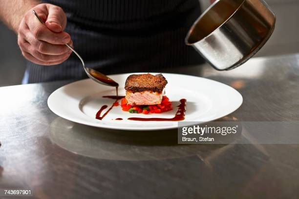 Salmon fillet and gravy being arranged on a plate