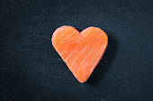 Salmon fillet copy space black slate background, healthy eating omega 3 concept. Heart shaped salmon steak.