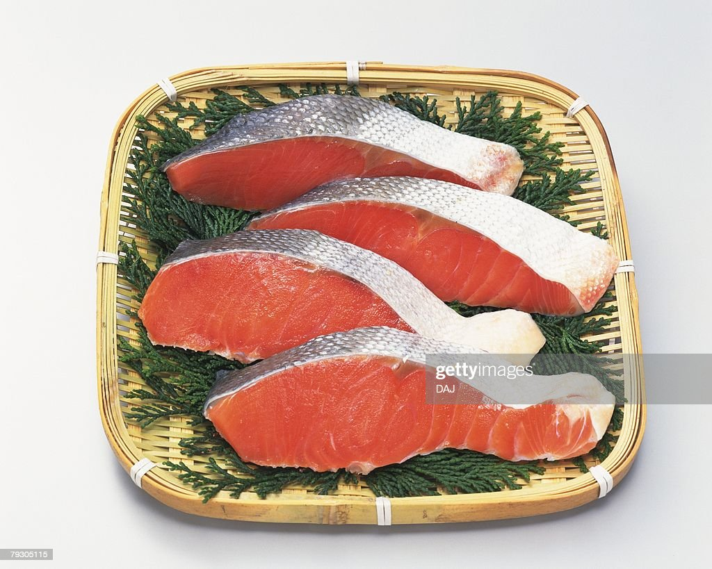 Salmon fillets on bamboo basket, high angle view : Stock Photo