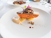 elegant white circular plate with salmon piece, mayonnaise, potato and mushroom and color leaves on white tablecloth in restaurant