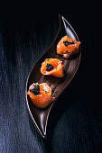 Plate of salmon rolls with black caviar over black textured surface
