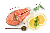 An overhead photo of a raw salmon steak with dill, lemons, and peppercorns, shot from above on a white background with a place for text