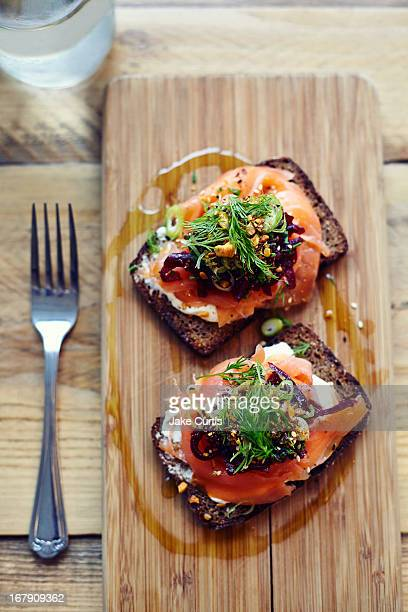 salmon tartine on rye bread on wooden board