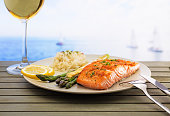 Salmon with asparagus and rice . Freshly served with a glass of wine and sea view .