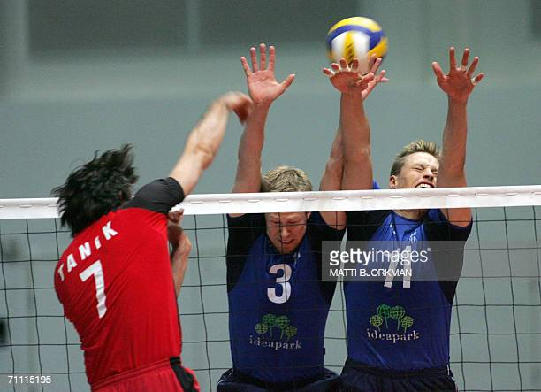 Sinan Cem Tanik of team Turkey hits the ball through Finnish defence made by Mikko Esko and Janne Heikkinen in mens volleyball European Championships...