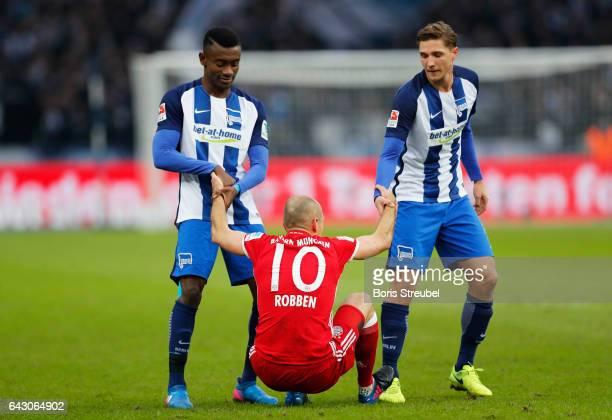 Salomon Kalou of Hertha BSC and Niklas Stark of Hertha BSC give Arjen Robben of FC Bayern Muenchen a legup during the Bundesliga match between Hertha...