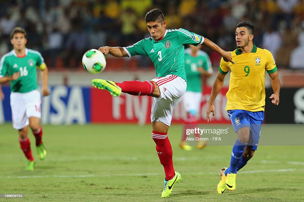 Salomon Wbias of Mexico clears the ball ahead of Mosquito of Brazil during the FIFA U-17 World Cup UAE 2013 Quarter Final match between Brazil and Mexico at Al Rashid Stadium on November 1, 2013 in Dubai, United Arab Emirates.