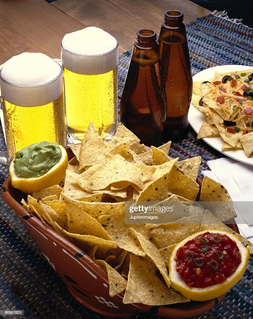 Salsa and guacamole with tortilla chips and beers : Stock Photo