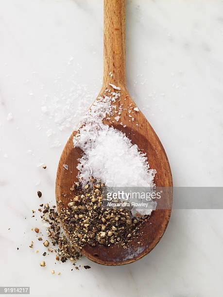 Salt and pepper on wooden spoon