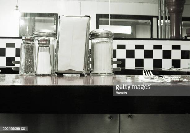 Salt and pepper shakers, sugar, napkins and cutlery on diner table
