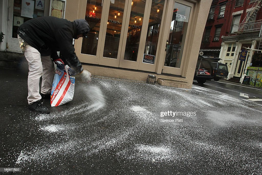 Salt is thrown on a sidewalk as Manhattan prepares for a major winter storm on February 8, 2013 in New York City. New York City and much of the Northeast is expected to get a foot or more of snow through Saturday afternoon with possible record-setting blizzard conditions expected. Heavy snow warnings are in effect from New Jersey through southern Maine.