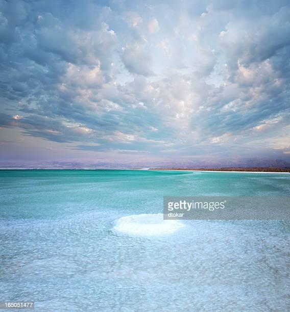 死海の塩に島の夕日と雲の中にあります。イズラエル