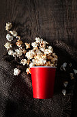 Salt popcorn in a red cardboard box on the wooden table, Cinema concept