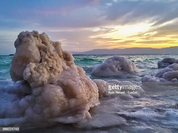 Salt Rocks In Dead Sea Against Sky During Sunrise