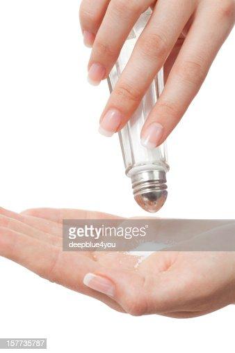 Salt shaker in woman hand on white