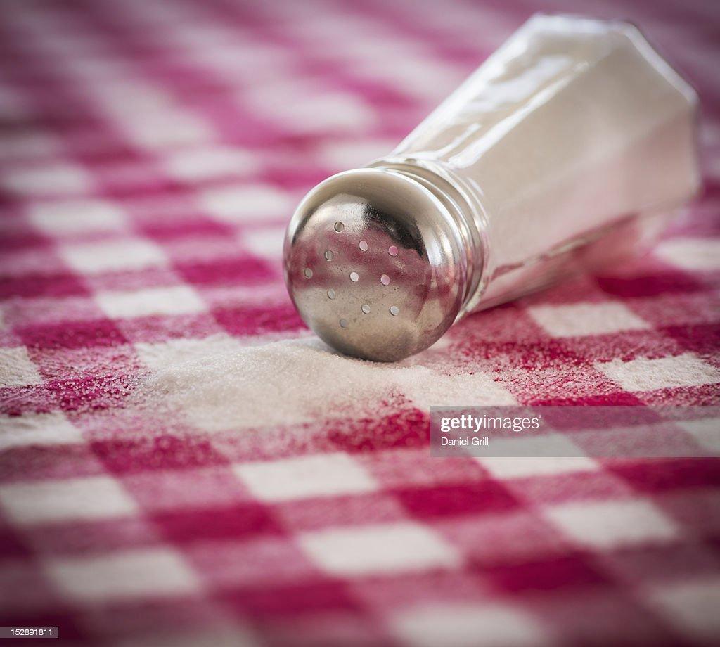 Salt shaker on checked tablecloth