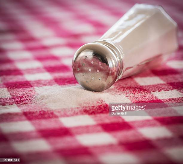 Salt shaker on checked tablecloth