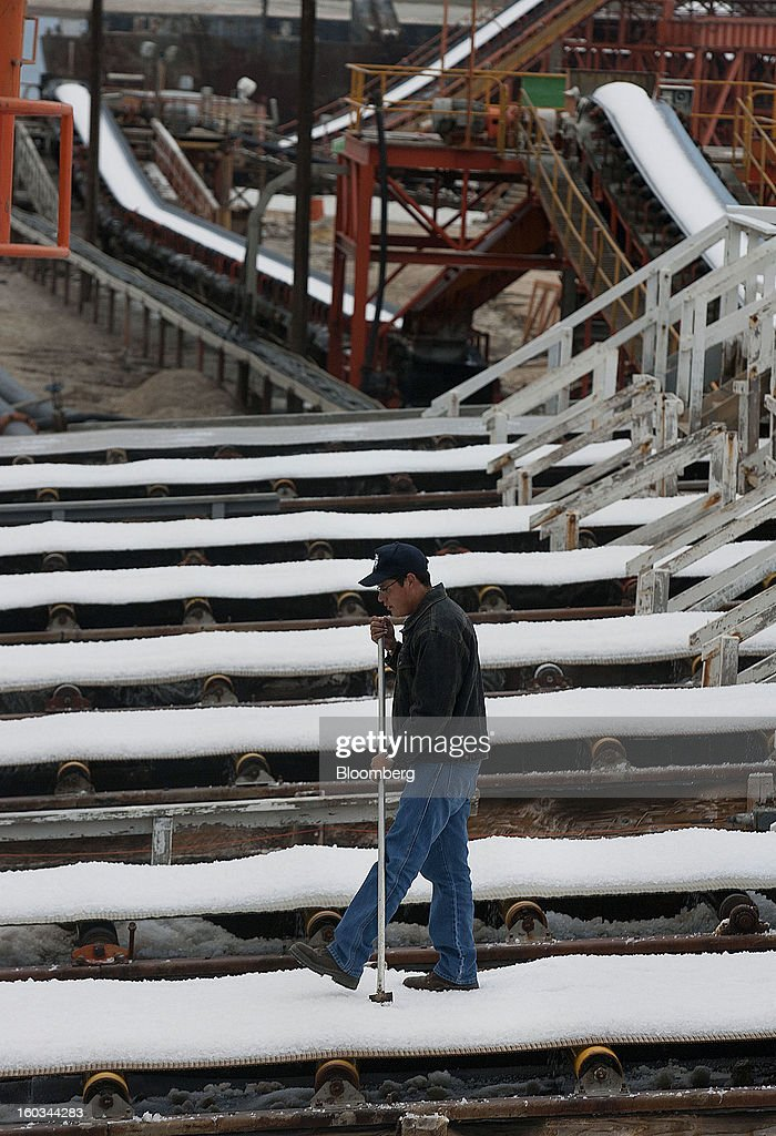 Salt washer Martin Sandez inspects liquids used for washing salt on the conveyor belt at the Exportadora de Sal (ESSA) facility in Guerrero Negro, Mexico, on Wednesday, Jan. 24. 2013. Exportadora de Sal (ESSA), a joint venture between Fidecomiso Mining Development Corporation and Mitsubishi, is one of the leading producers and suppliers of salt for the chlorine-alkali industry in the Pacific Rim. Photographer: Susana Gonzalez/Bloomberg via Getty Images
