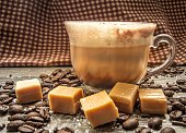 Salted caramel latte surrounded by coffee beans, caramels, and sea salt. Shot from a side view with selective focus and a rustic gingham background.
