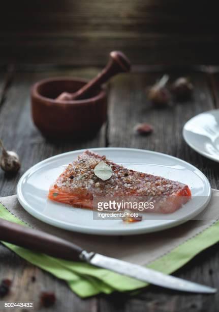 Saumon salé avec gros sel et des cristaux de sucre sur le dessus sur la vieille table en bois.