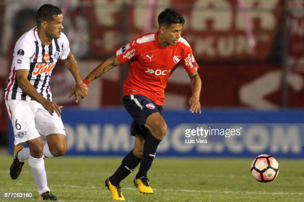 Salustiano Candia of Libertad fights for the ball with Maximiliano Meza of Independiente during a first leg match between Libertad and Independiente...