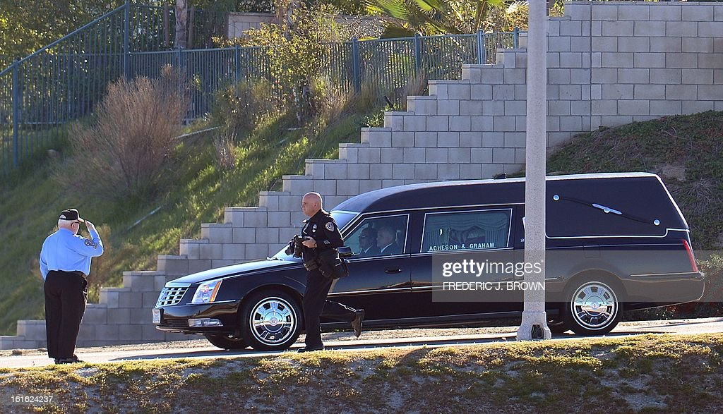 A salute is offered to the passing hearse carrying the body of slain Riverside police officer Michael Crain on its approach to the Grove Community Church in Riverside, California, on February 13, 2013. Law enforcement personnel from across the state, and others close to the deceased gathered to pay their final respects to the policeman killed last week in what the city's police chief described as a 'cowardly ambush.'' Crain was fatally shot last Thursday when he and his partner ran afoul of fugitive Christopher Jordan Dorner, the fired Los Angeles Police Department officer on a killing spree which ended last night in the mountains of nearby Big Bear, authorities report. AFP PHOTO / Frederic J. BROWN