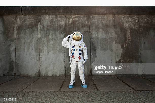 A saluting astronaut standing on a sidewalk in a city