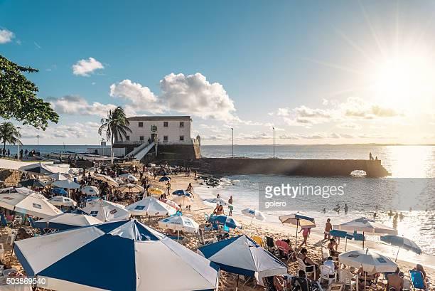 Salvador de Bahia, affollata spiaggia con ombrelloni al tramonto