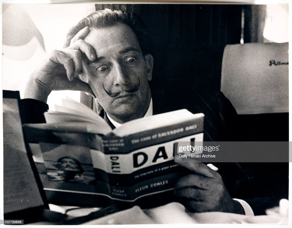 Salvador Dali reading his biography, 6 May, 1959. A photograph of the Spanish artist Salvador Dali (1904-1989), taken by Terry Fincher for the Daily Herald newspaper. Dali is reading Fleur Cowles' book 'The Case of Salvador Dali' (1959), whilst on a train from Folkestone, having travelled from France. Cowles' book was an authorised biography of Dali. With a studied expression of shock on his face, Dali enjoys the photo opportunity. One of the most famous, charismatic and notorious artists of the twentieth century, Dali devoted himself to drawing and painting from an early age. Hugely influential as a Surrealist, one of his most famous paintings is 'The Persistence of Memory'. By the 1950s Dali had turned to demonstrating scientific, historical and religious themes in his work. In later life he founded both the Dali Theatre-Museum, Figueres, Spain and the Gala-Salvador Dali Foundation, Pubol Castle, Spain - the latter to manage his legacy.