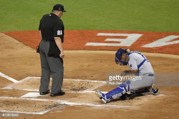 Salvador Perez of the Kansas City Royals and the American League reacts after being hits a by a foul tip off the bat of Buster Posey of the San...