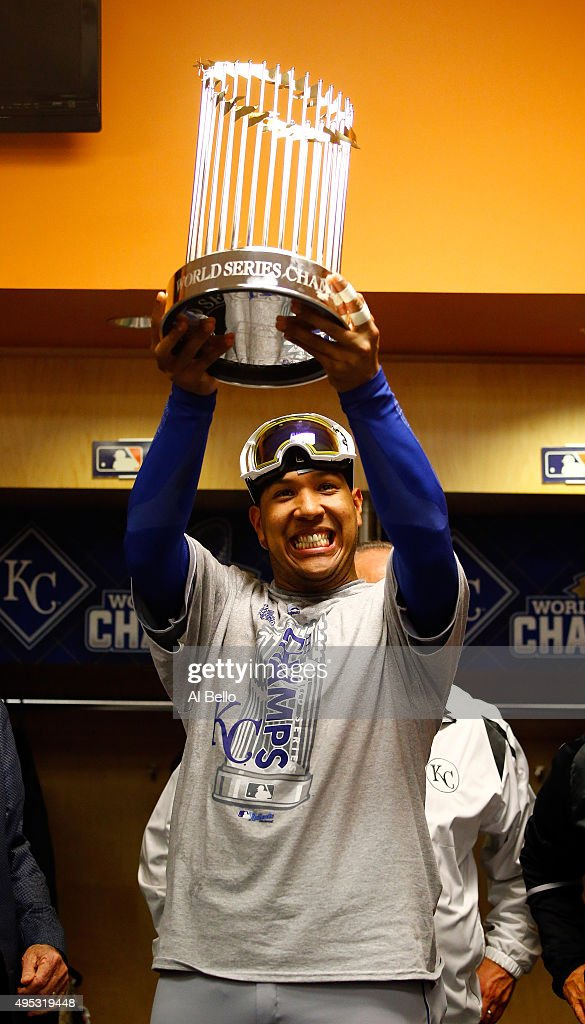 Salvador Perez #13 of the Kansas City Royals celebrates in the clubhouse with the Commissioner's Trophy after defeating the New York Mets to win Game Five of the 2015 World Series at Citi Field on November 1, 2015 in the Flushing neighborhood of the Queens borough of New York City. The Kansas City Royals defeated the New York Mets with a score of 7 to 2 to win the World Series.