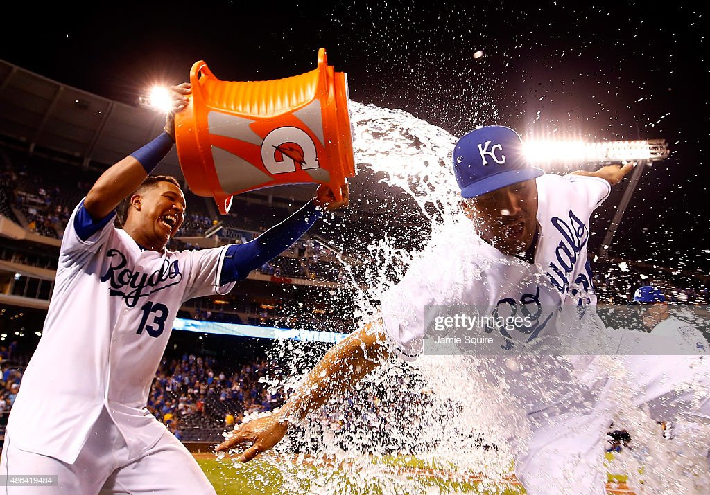 Salvador Perez #13 of the Kansas City Royals douses Kendrys Morales #25 with a bucket of water after the Royals defeated the Detroit Tigers 15-7 to win the game against the Detroit Tigers at Kauffman Stadium on September 3, 2015 in Kansas City, Missouri.