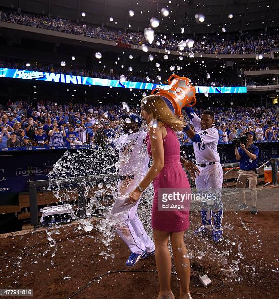 Salvador Perez of the Kansas City Royals douses Lorenzo Cain of the Kansas City Royals and a NESN field reporter with water after a 74 win over the...