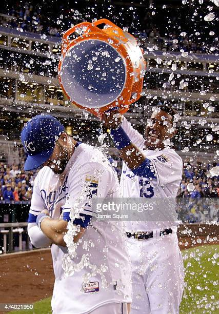 Salvador Perez of the Kansas City Royals dumps a bucket of water over the head of Mike Moustakas after the Royals defeated the Cincinnati Reds 30 to...