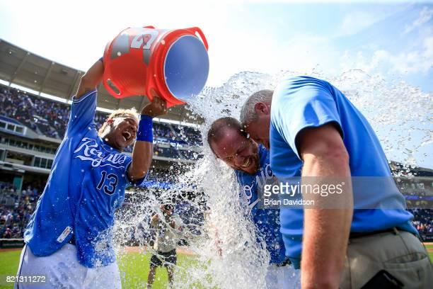 Salvador Perez of the Kansas City Royals dumps water onto Brandon Moss and Joel Goldberg of Fox Sports after Moss hit the game winning walk off RBI...