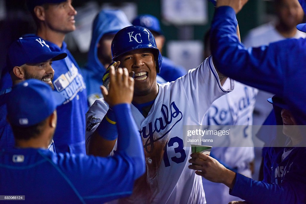 Salvador Perez #13 of the Kansas City Royals high fives teammates in the dugout after sliding home to score a run in the eighth inning against the Boston Red Sox at Kauffman Stadium on May 17, 2016 in Kansas City, Missouri.