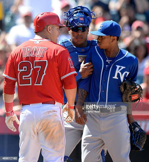 Salvador Perez of the Kansas City Royals holds back Yordano Ventura from Mike Trout of the Los Angeles Angels after his run to trail 72 during the...