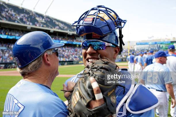 Salvador Perez of the Kansas City Royals is congratulated by closing pitcher first base coach Rusty Kuntz after the Royals defeated the Boston Red...