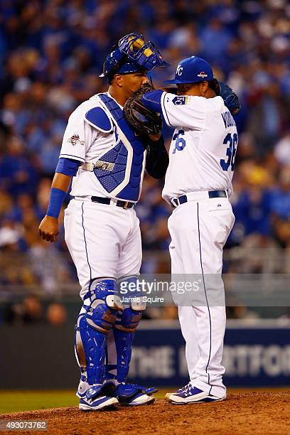 Salvador Perez of the Kansas City Royals meets with Edinson Volquez of the Kansas City Royals on the pitcher's mound during game one of the American...