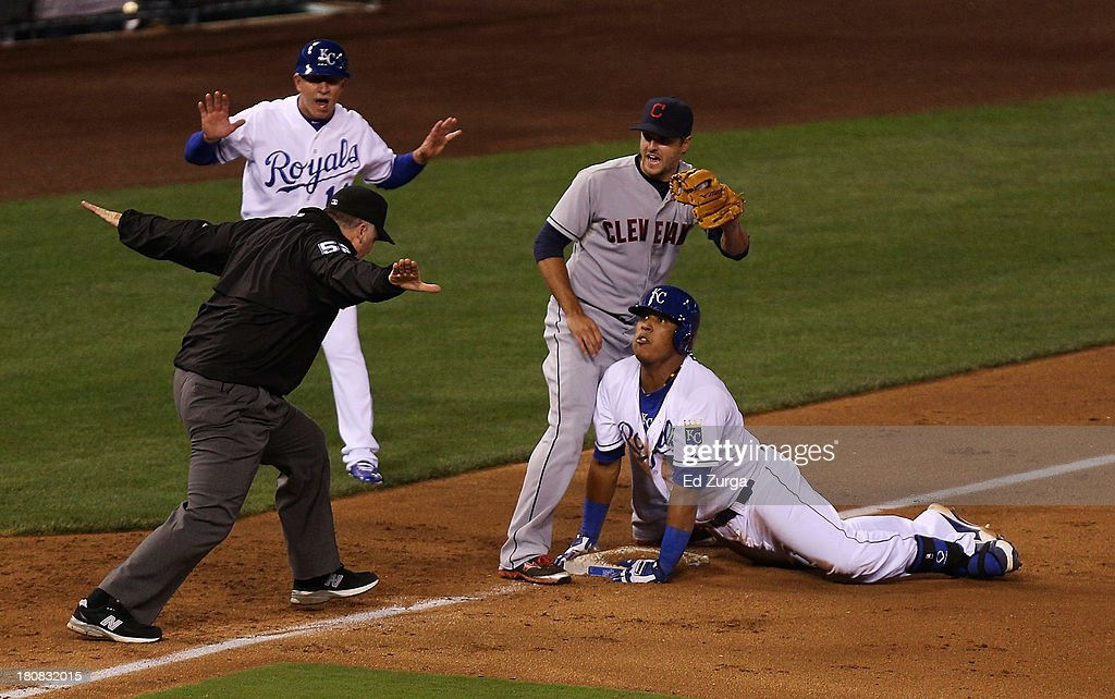 Salvador Perez #13 of the Kansas City Royals reacts as third base umpire Bill Welke calls him safe on a triple as Lonnie Chisenhall #8 of the Cleveland Indians looks on in the sixth inning at Kauffman Stadium on September 16, 2013 in Kansas City, Missouri.