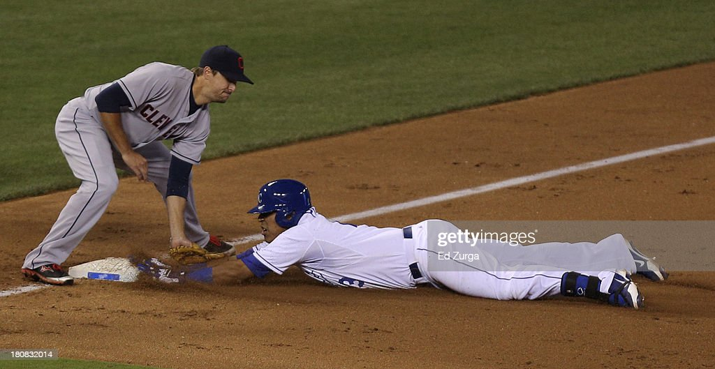 Salvador Perez #13 of the Kansas City Royals slides into third past the tag of Lonnie Chisenhall #8 of the Cleveland Indians for a triple in the sixth inning at Kauffman Stadium on September 16, 2013 in Kansas City, Missouri.