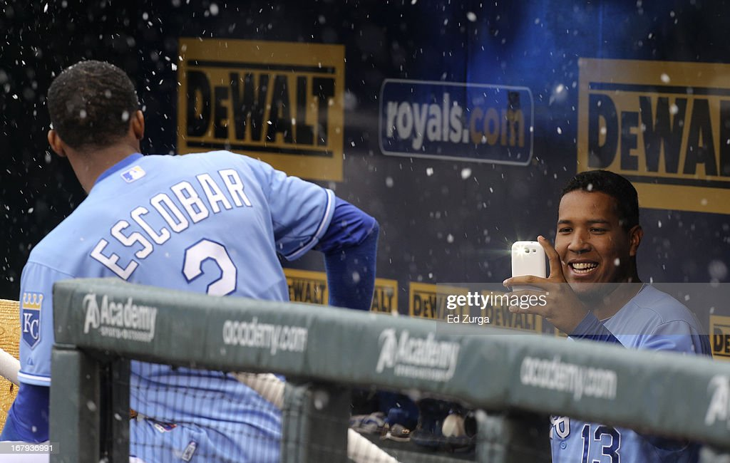 Salvador Perez #13 of the Kansas City Royals takes a photo of teammate <a gi-track='captionPersonalityLinkClicked' href=/galleries/search?phrase=Alcides+Escobar&family=editorial&specificpeople=4845889 ng-click='$event.stopPropagation()'>Alcides Escobar</a> #2 as snow falls during a delay in a game against the Tampa Bay Rays at Kauffman Stadium on May 2, 2013 in Kansas City, Missouri. The game was postponed due to weather.