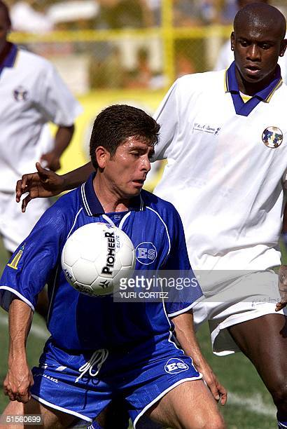 Salvadoran Mauricio Cienfuegos controls the ball 23 July 2000 as he encounters defender Ezra Hendrickson of St Vincent's selectin in San Salvador El...